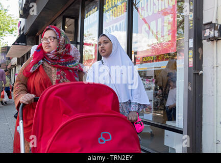 Two Muslim women in hijabs, probably sisters, walk down 74th St. in Jackson Heights pushing a red baby stroller. Queens, NYC. - Stock Image