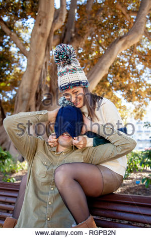 A couple plays with a woolen hat in a public park - Stock Image