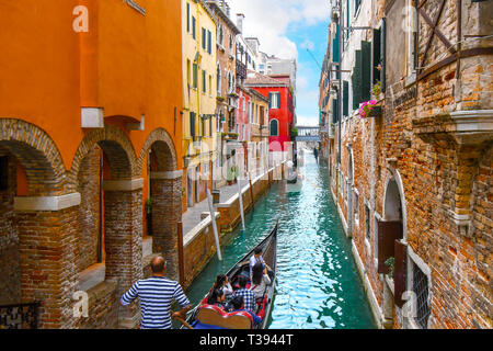 Gondoliers in line as they maneuver their gondolas filled with tourists through a narrow canal in Venice, Italy. - Stock Image