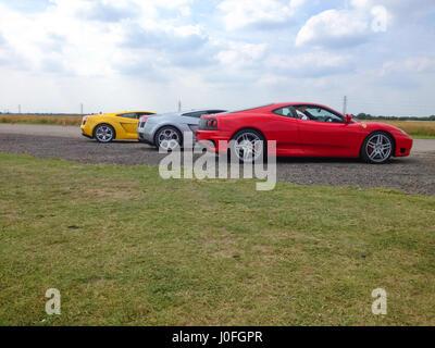 Three Super Sars - Red Ferrari 488, Silver Lamborghini Murcielago, Yellow Lamborghini Murcielago - Stock Image