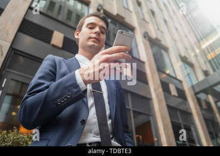 Close up of businessman next to skyscraper at downtown holding mobile phone and looking at screen. Bottom view - Stock Image