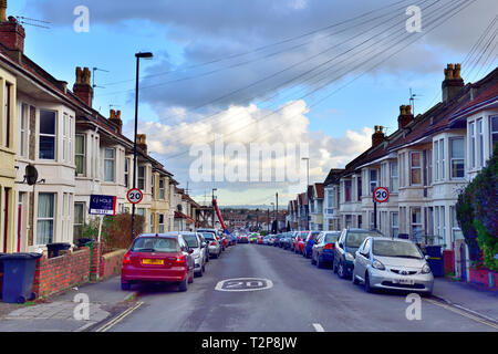 Looking down street of terraced bay windowed suburban houses in Filton with 20 mph speed signs, suburb of Bristol, England, UK - Stock Image
