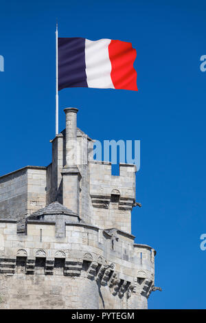 The French national flag flying from the tower of  La Tour de la Lanterne in the port of La Rochelle in the Charente-Maritime region of France. - Stock Image