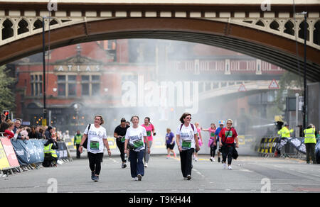 Competitors complete the Simply Health Manchester Run. - Stock Image