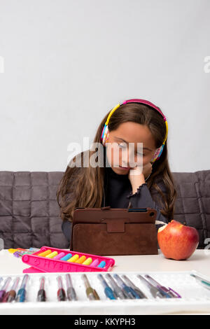 Thinking child bored, frustrated and fed up doing his homework - Stock Image