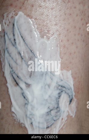 freshly inked wing tattoo on male ankle covered in Bepanthen cream to aid healing - Stock Image