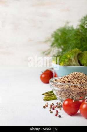 healthy diet food. quinoa in a glass bowl, cherry tomatoes, asparagus, broccoli on a light background concrete - Stock Image