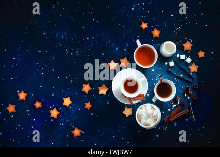 Teatime with star-shaped cookies. White porcelain cups on a starry sky background. Astronomy and constellation flat lay with copy space - Stock Image
