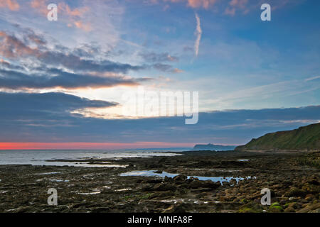 Coastal rock pools reflect the morning sky as the sun rises at Crook Ness, near Scarborough. - Stock Image