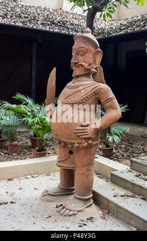 Exhibit of stone carvings of a fat man typical of Rajasthan in the National Crafts Museum, New Delhi, India - Stock Image
