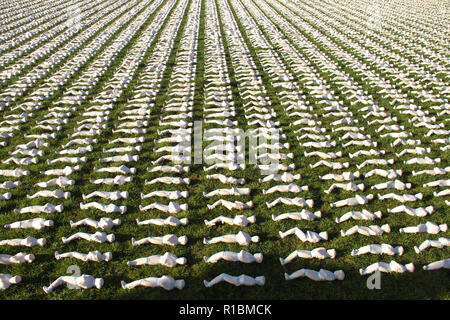 London's Queen Elizabeth Olympic Park, Stratford, London - 11 November  2018: Shrouds of the Somme art installation which represents the 72,396 British Commonwealth servicemen killed at the Battle of the Somme who have no known grave, and whose names are engraved on the Thiepval Memorial seen in remembrance day Sunday 2018. Hundreds of people were silent for two minutes in honour of the fallen. The installation is made up of hand-sewing calico shrouds and bound over small figures by artist Rob Heard. Credit: David Mbiyu /Alamy Live News - Stock Image