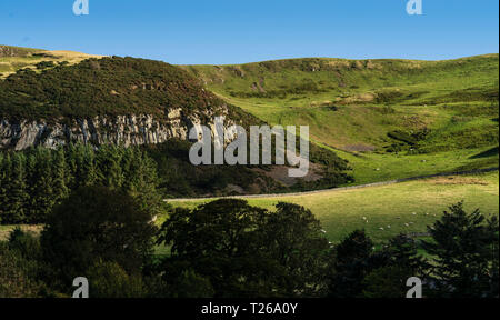 Border scenery in the Cheviot hills where Scotland joins England. Crags near Kirk Yetholm, end of the Pennine Way, with Staerough hill beyond. - Stock Image