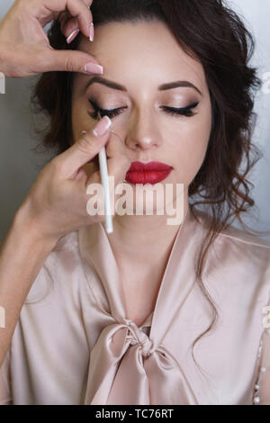 Make-up artist working in make-up studio applies arrows to eyelid with a brush. Female face close up view straight. - Stock Image