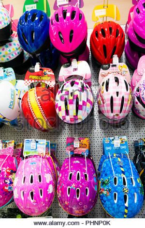 Children's cycle helmets for sale in a store, UK. - Stock Image