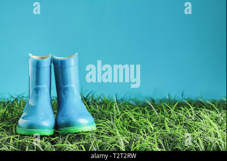 Blue children's rain boots / wellies sitting in the grasss agaisnt a blue background with room for copy space. - Stock Image