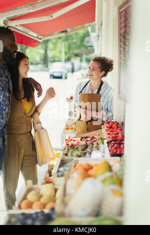 Female worker helping young couple shopping for fruit at market storefront - Stock Image