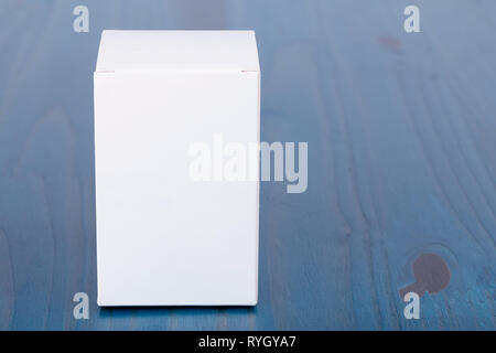A white cardboard box on wooden background painted blue. - Stock Image