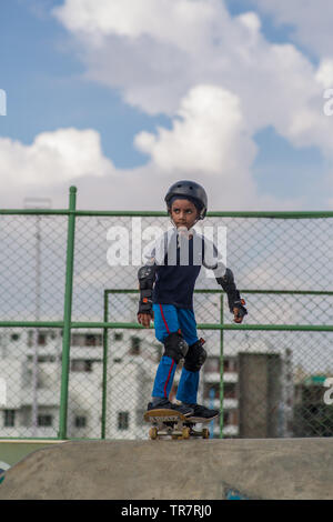 A indian kid preparing to go down a skateboard ramp - Stock Image