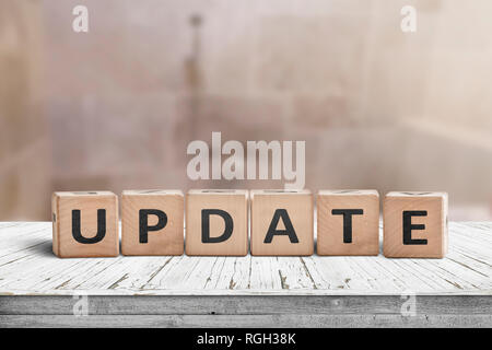 Update message sign on a wooden desk in a room with a blurry background - Stock Image