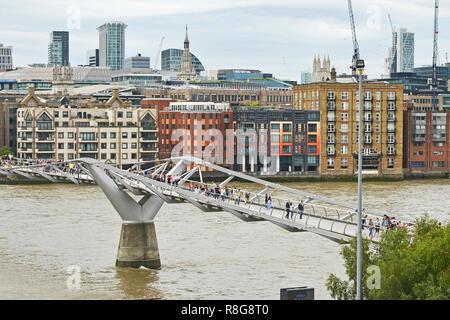THE MILLENNIUM BRIDGE, THAMES EMBANKMENT, LONDON. AUGUST 2018. The Millennium Footbridge a suspension bridge over the River Thames with the skyline of - Stock Image