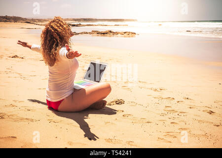 Happy free people caucasian woman sit at the ebach with computer laptop on her legs opening arms enjoying the freedom for vacation summer and for work - Stock Image