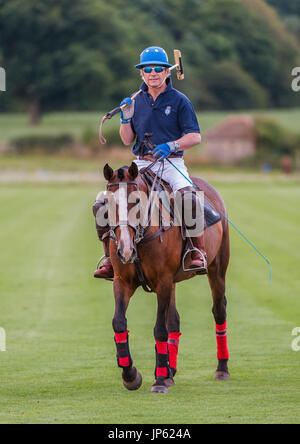 Leadenham Polo Club, Lincolnshire, England - A polo match being played on a shot summers afternoon as a gent leaves the polo pitch - Stock Image