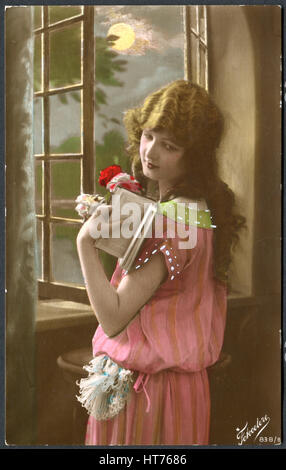 ITALY - CIRCA 1920: A postcard printed in Italy, shows a sad girl standing at the window with a book, circa 1920 - Stock Image