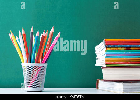 Image of crayons and exercise books against blackboard - Stock Image