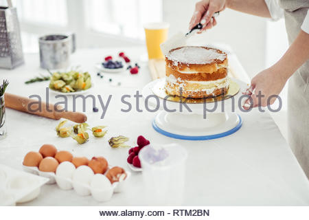 talented chef assembling the cake layers. detail steps on how to make cake, close up cropped photo - Stock Image