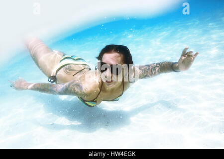 Young woman swims underwater sea - Stock Image