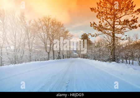 Mountain road with snow in winter at sunset - Stock Image