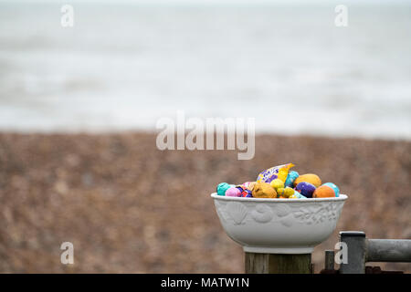 easter eggs in bowl on beach - Stock Image