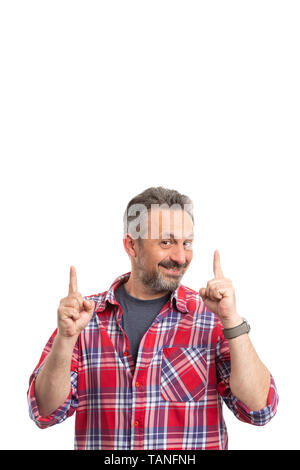 Smiling man pointing index fingers at blank copyspace for text above head isolated on white background - Stock Image