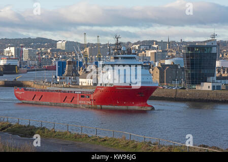 North sea offshore supply vessel leaving the commercial harbour of Aberdeen docks in Grampian Region Scotland UK. - Stock Image