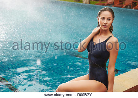 Young woman sitting by swimming pool - Stock Image