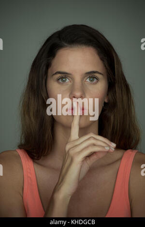 Young woman holding finger against lips in silence, portrait - Stock Image