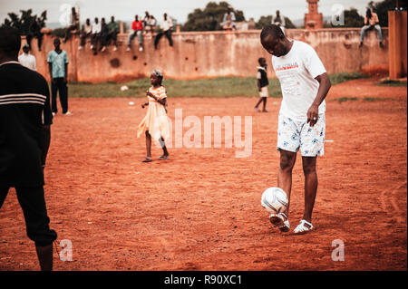 Mali, Africa - Black african children, boys and adults playing soccer in a rubbish dump. Rural area near Bamako - Stock Image