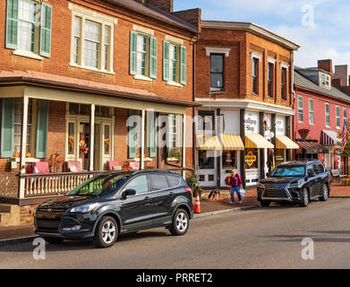 JONESBOROUGH, TN, USA-9/29/18:  A woman and her dog walk along main street in Jonesborough, which is decorated for Thanksgiving. - Stock Image