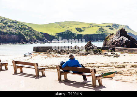 Hope Cove, Devon, UK, England, Hope Cove Devon, Man looking out to sea, sitting on bench, leaning on bench, overlooking sea, enjoying view, relaxing, - Stock Image
