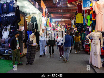 Marrakech souk - local people and tourists shopping in the souks; the Marrakesh Medina, Marrakech, Morocco, North Africa - Stock Image