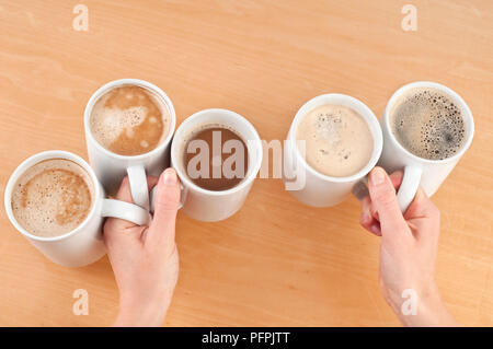 Two hands holding six mugs of coffee, hot chocolate, latte, and espresso above wooden desk, overhead view - Stock Image