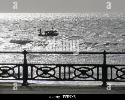 A fishing boat struggles against a westerly tide off Hove Lawns promenade in the early morning sunlight in the glistening - Stock Image