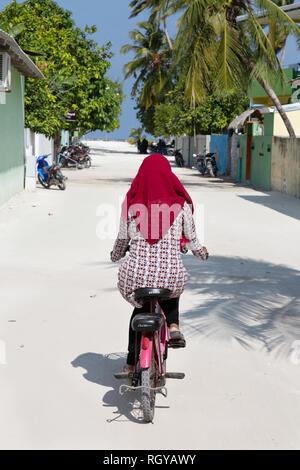 Maldives lifestyle - a muslim woman cycling, Ukulhas island, Alif Alif atoll, the Maldives Asia - Stock Image