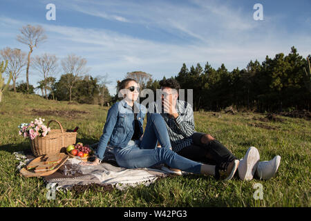 man and woman with glasses sitting on a blanket enjoying a sunny picnic afternoon - Stock Image