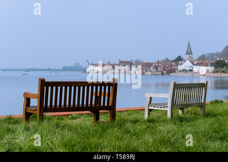 Two empty benches overlooking Bosham Creek and village at high tide in Chichester harbour. Bosham, West Sussex, England, UK, Britain - Stock Image