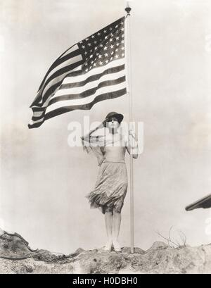 Patriotic woman holding American flag and saluting - Stock Image
