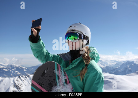 Young female snow boarder photographing view, Mayrhofen, Tyrol, Austria - Stock Image
