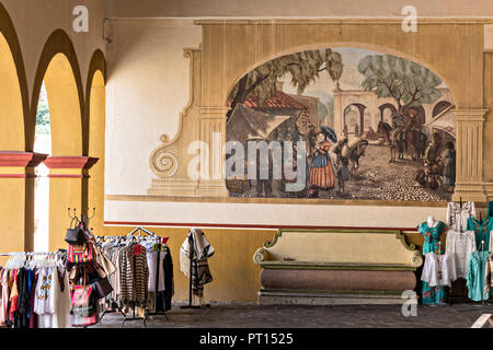 Painted mural and stone bench in the beautiful colonial village of Bernal, Queretaro, Mexico. Bernal is a quaint colonial town known for the Pena de Bernal, a giant monolith which dominates the tiny village is the third highest on the planet. - Stock Image