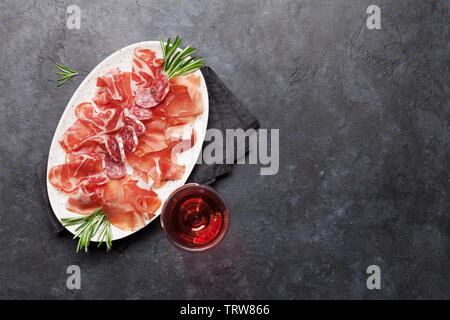 Traditional spanish jamon, prosciutto crudo, italian salami, parma ham. Antipasto plate and glass of wine. Top view flat lay. With copy space - Stock Image