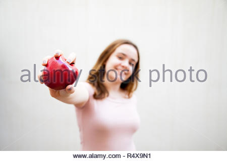 Teenage girl holds a red apple with her hands and offers it - Stock Image